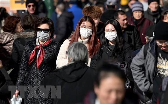Người dân đeo khẩu trang để phòng tránh lây nhiễm COVID-19 tại New York, Mỹ. (Ảnh: AFP/TTXVN)