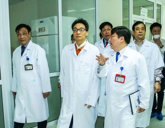 Phó Thủ tướng Vũ Đức Đam (giữa) nghe lãnh đạo BV Bệnh Nhiệt đới Trung ương báo cáo công tác phòng, chống dịch viêm hô hấp cấp Corona. Ảnh: Đình Nam