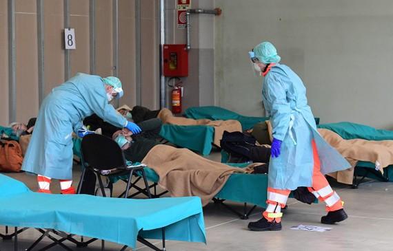 Nhân viên y tế điều trị cho bệnh nhân mắc COVID-19 tại một bệnh viện dã chiến ở vùng Lombardy, Italy. (Ảnh: AFP/TTXVN)
