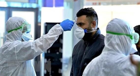 Nhân viên y tế kiểm tra thân nhiệt của người dân trong bối cảnh dịch COVID-19 lan rộng tại Tehran, Iran. (Ảnh: IRNA/ TTXVN)