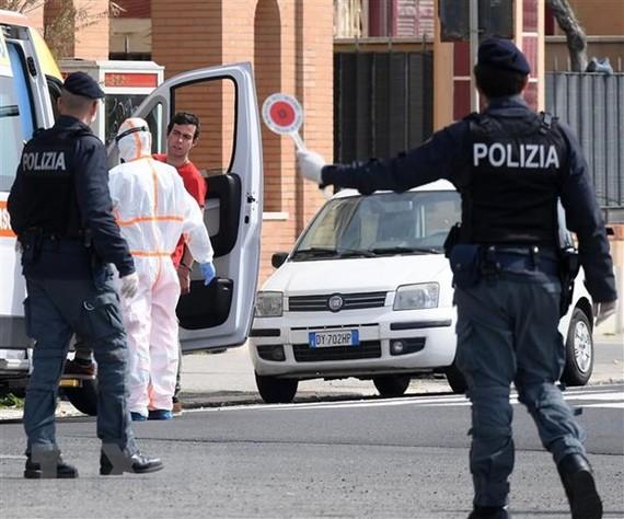 Cảnh sát và nhân viên y tế được triển khai tới nơi ở của bệnh nhân nhiễm COVID-19 tại Rome, Italy. (Ảnh: THX/TTXVN)