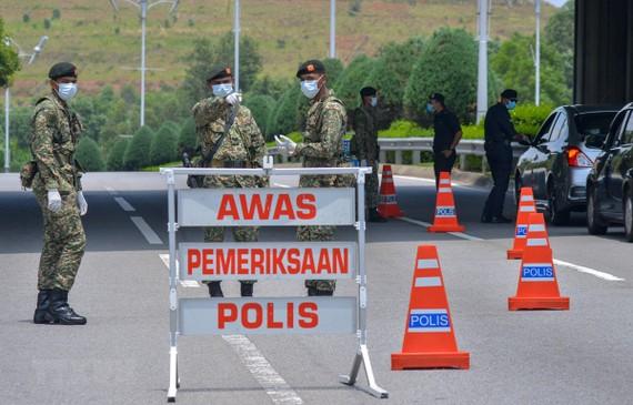 Cảnh sát và binh sỹ phong tỏa một khu vực ở Putrajaya, Malaysia trong bối cảnh dịch COVID-19 lan rộng. (Ảnh: THX/TTXVN)