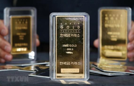 Nhân viên giới thiệu các thanh vàng tại cửa hàng ở Seoul, Hàn Quốc. (Ảnh: YONHAP/TTXVN)