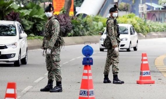 Các binh sĩ canh gác trên một con đường ở thủ đô Kuala Lumpur, Malaysia, ngày 22/3. Ảnh:Reuters.
