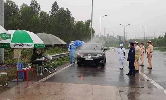 Phun khử khuẩn đối với xe ôtô ra vào tỉnh ở đường nhánh rẽ vào cao tốc Nội Bài-Lào Cai. (Ảnh: Nguyễn Thảo/TTXVN)
