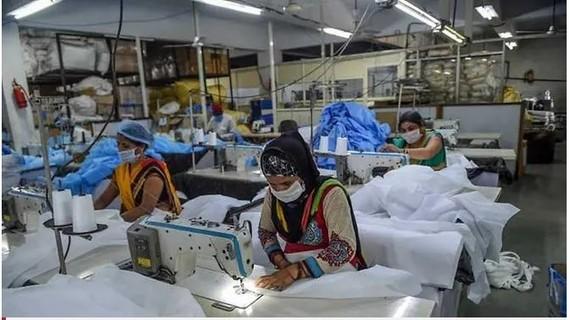 Công nhân may quần áo bảo hộ y tế tại một cơ sở của thành phố Ahmedabad, Ấn Độ, Ảnh AFP