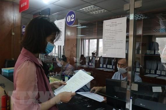 Người dân nhận giấy đăng ký kinh doanh. (Ảnh Mạnh Khánh/TTXVN)