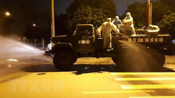 Lực lượng quân đội phun khử khuẩn toàn bộ đường giao thông trên địa bàn thôn Hạ Lôi, Mê Linh. (Ảnh: Nguyễn Cúc/TTXVN)