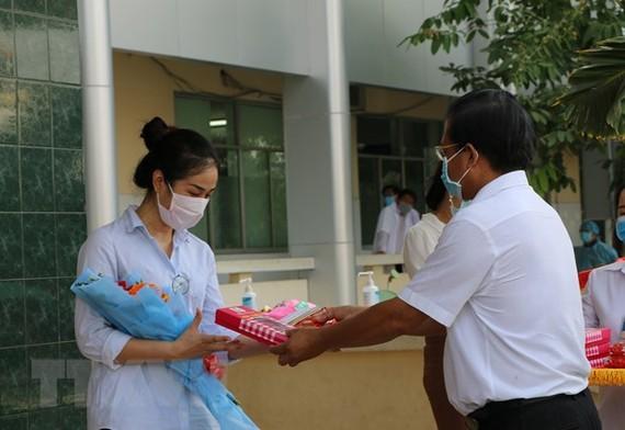 Trao quà và trao giấy xuất viện cho trường hợp mắc COVID-19 sau thời gian điều trị, tại Bệnh viện Đa khoa Sa Đéc, Đồng Tháp. (Ảnh: Chương Đài/TTXVN)