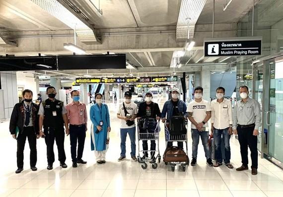 Nhóm công dân Việt Nam cùng cán bộ Đại sứ quán Việt Nam tại Thái Lan và nhân viên Vietnam Airlines trước giờ lên máy bay. (Ảnh: TTXVN)