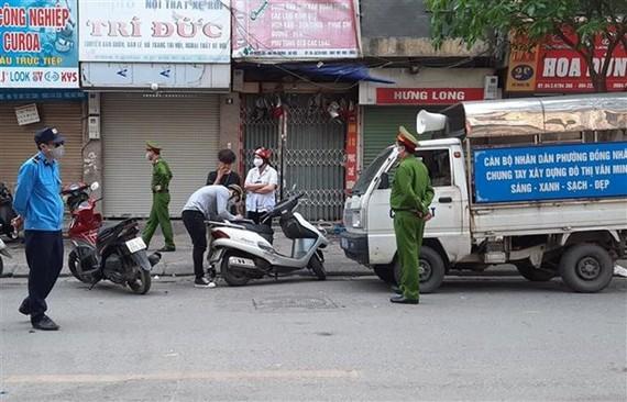 Tổ công tác phường Đồng Nhân (quận Hai Bà Trưng, Hà Nội) xử phạt các trường hợp vi phạm không đeo khẩu trang ra đường. (Ảnh: Doãn Tấn/TTXVN)