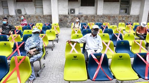 Bệnh viện Thống Nhất (TP.HCM) căng dây các ghế ngồi để giữ khoảng cách an toàn giữa các bệnh nhân - Ảnh: DUYÊN PHAN