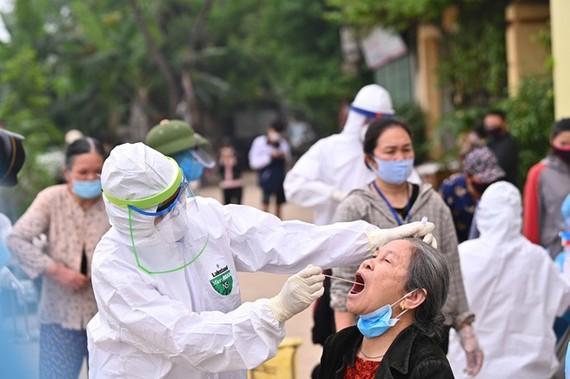 Lấy mẫu xét nghiệm SARS-CoV-2 cho người dân thôn Hạ Lôi. Ảnh: Báo SK&ĐS