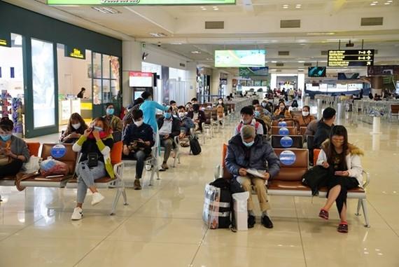 Hành khách tuân thủ giữ khoảng cách khi ngồi tại nhà ga tại sân bay Nội Bài. (Ảnh: Phan Công/Vietnam+)