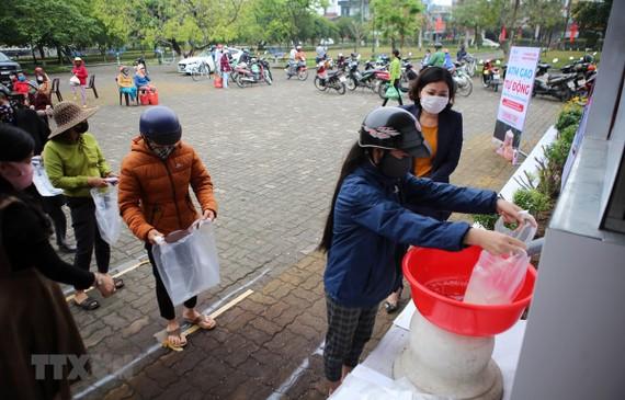 Người dân nhận gạo tại cây ATM gạo tự động. (Ảnh: Hồ Cầu/TTXVN)
