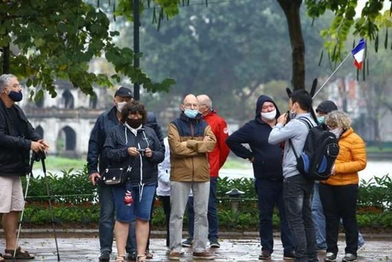 Du khách nước ngoài đeo khẩu trang khi đi tham quan Hà Nội. (Ảnh: Minh Quyết/TTXVN)