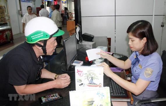 Nhân viên tại Ga Sài Gòn hướng dẫn hành khách thủ tục mua vé tàu. (Ảnh: Tiến Lực/TTXVN)