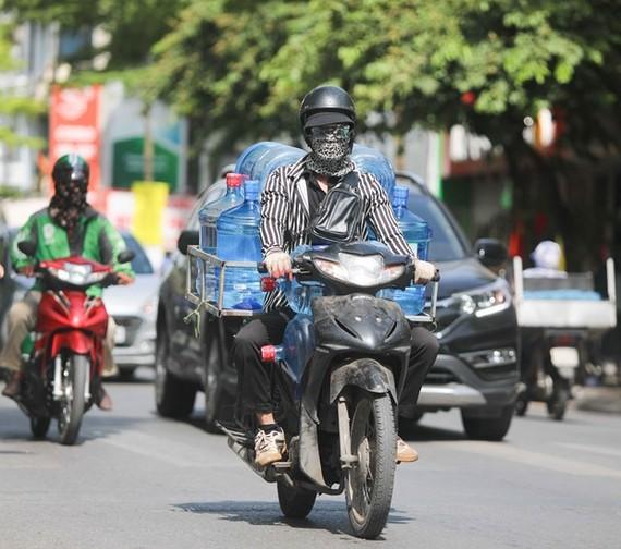 Thời tiết nắng nóng, tia UV ở mức cao, người dân cần trang bị tốt đồ bảo hộ khi ra đường để bảo vệ sức khỏe. (Ảnh: Thanh Tùng/TTXVN)