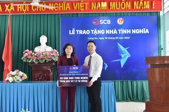 Ông Đinh Văn Thành – Chủ tịch HĐQT SCB trao bảng tượng trưng trao 20 căn nhà tình nghĩa tại Long An.