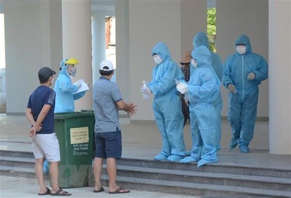 Nhân viên y tế thực hiện quy trình tiếp đón các trường hợp F1 được cách ly tại Khu ký túc xá phía Tây thành phố Đà Nẵng. (Ảnh: Văn Dũng/TTXVN)