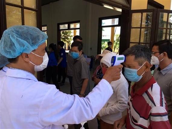 Hành khách đi trên những phương tiện giao thông tiến hành kiểm tra thân nhiệt, khai báo y tế tại chốt kiểm tra thị xã Hương Thủy, tỉnh Thừa Thiên-Huế. (Ảnh: Đỗ Trưởng/TTXVN)