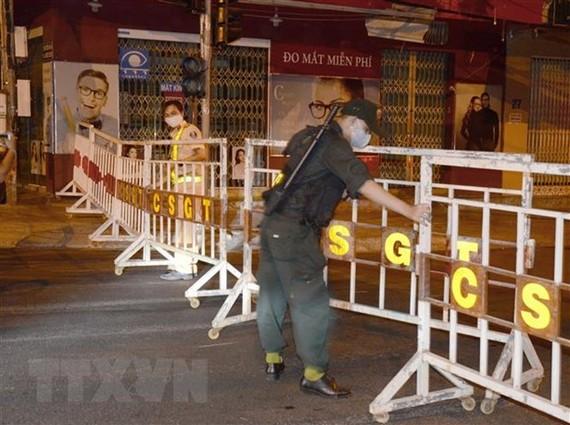 Lực lượng chức năng lập hàng rào phong tỏa và chốt chặn khu vực bị cách ly. (Ảnh: Quốc Dũng/TTXVN)