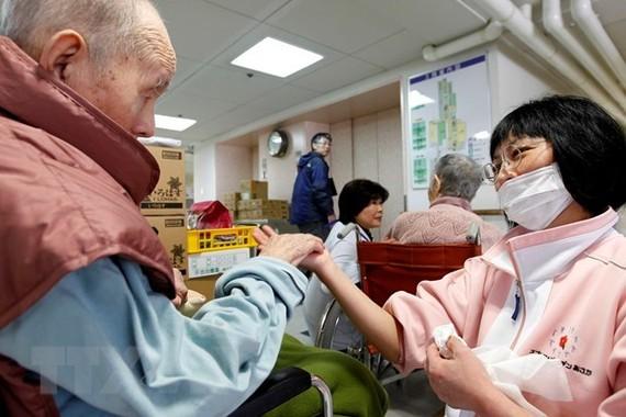 Điều dưỡng viên hỗ trợ người cao tuổi tại Tomioka, tỉnh Fukushima, Nhật Bản. (Ảnh minh hoạ: AFP/TTXVN)