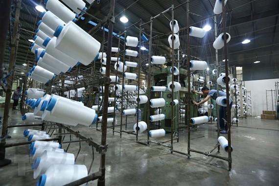 Công nhân làm việc tại nhà máy sợi Huế thuộc Công ty Cổ phần Dệt may Huế (Thừa Thiên-Huế). (Ảnh: TTXVN)