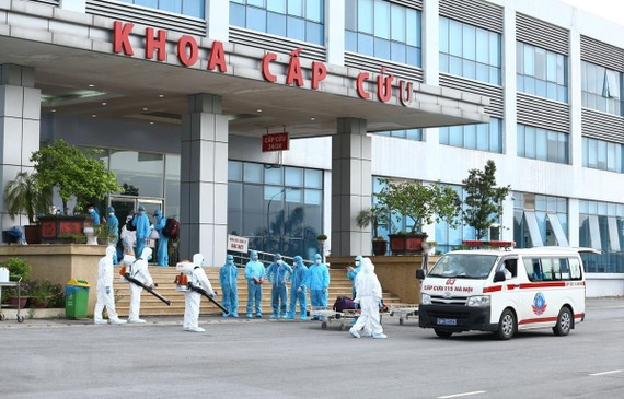 Lực lượng y tế phun thuốc khử khuẩn các công dân khi được đưa về Bệnh viện Nhiệt đới Trung ương cơ sở 2. (Ảnh: Minh Quyết/TTXVN)