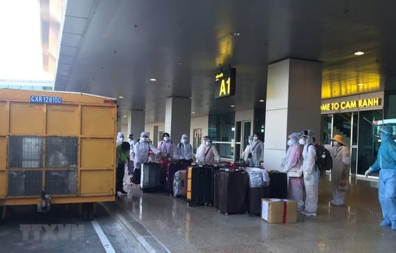 Công dân Việt Nam từ nước ngoài trở về chuẩn bị rời sân bay Cam Ranh đến khu cách ly tập trung. (Ảnh: Phan Sáu/TTXVN)
