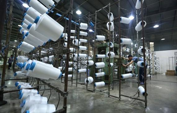 Công nhân làm việc tại nhà máy sợi Huế thuộc Công ty Cổ phần Dệt may Huế. (Nguồn: TTXVN)