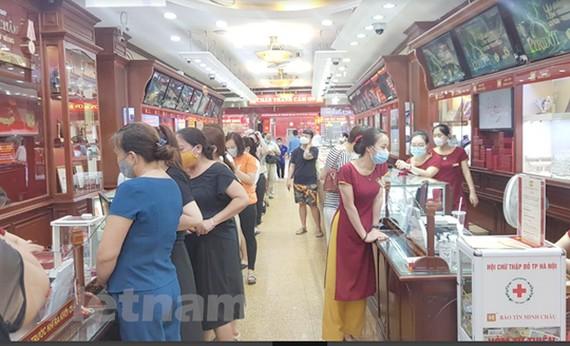 Nhiều người dân xếp hàng mua bán vàng tại Bảo Tín Minh Châu trên phố Trần Nhân Tông, Hà Nội chiều ngày 6/8. (Ảnh: PV/Vietnam+)