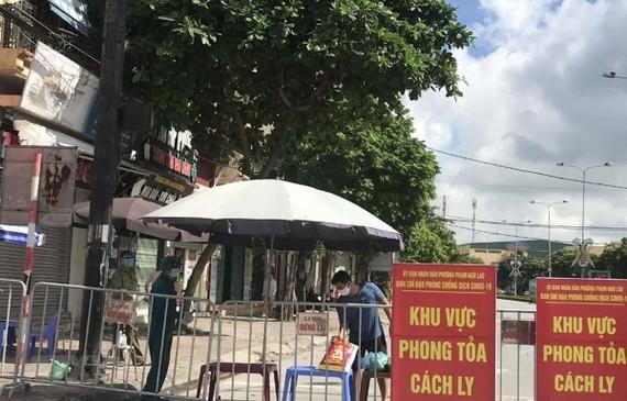 Người dân trong khu vực phong tỏa trên phố Ngô Quyền (Hải Dương) nhận thực phẩm tiếp tế tại hàng rào cách ly ngày 16/8. (Ảnh: Mạnh Minh/TTXVN)