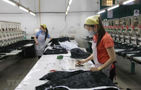 Công nhân Công ty TNHH Thêu Vĩnh Dương (quận Tân Phú) duy trì sản xuất trong những ngày dịch COVID-19. (Ảnh: Thanh Vũ/TTXVN)