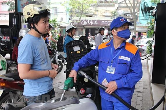 Nhân viên Petrolimex đang bán xăng cho khách hàng. (Ảnh: Đức Duy/Vietnam+)