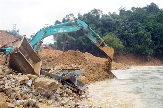 Các máy xúc đang tích cực hoạt động để tìm kiếm 12 công nhân bị mất tích tại Thủy điện Rào Trăng 3. (Nguồn: TTXVN phát)