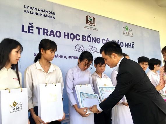 Đại diện Tập đoàn Novaland trao học bổng cho các em học sinh có hoàn cảnh khó khăn xã Long Khánh