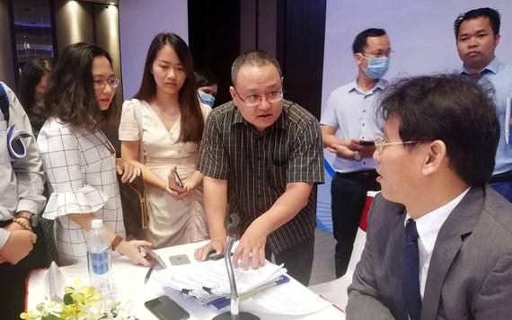 Đại diện doanh nghiệp lên bàn chủ tọa chất vấn ông Đặng Ngọc Minh (phó tổng cục trưởng Tổng cục Thuế) trong giờ giải lao - Ảnh: N.PHƯỢNG