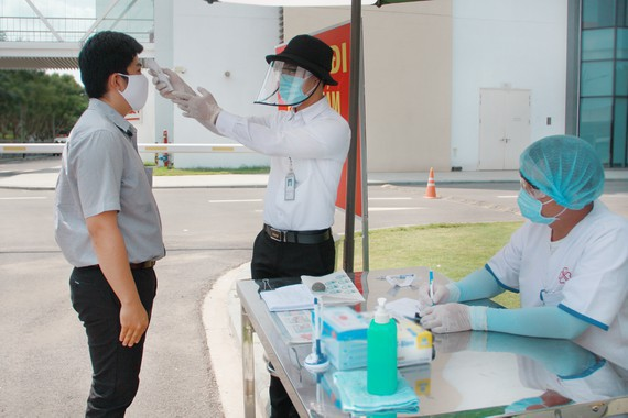 Nhân viên y tế kiểm tra thân nhiệt người nhà và bệnh nhân trước khi vào bệnh viện