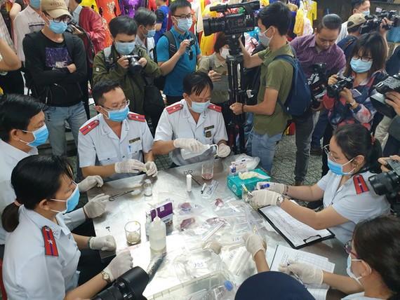 Ban quản lý an toàn thực phẩm TP.HCM lấy mẫu kiểm tra nhanh nhiều mặt hàng thực phẩm tại chợ Phạm Văn Hai - ẢNH: N.TRÍ
