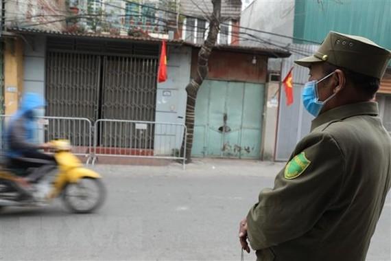Lực lượng chức năng tiến hành lập chốt tại khu vực có ca nghi nhiễm COVID-19 tại Hà Nội. (Ảnh: Minh Quyết/TTXVN)