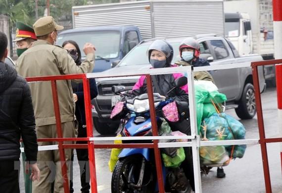 Người dân mang nhu yếu phẩm đến chốt kiểm dịch để cung cấp cho người thân trong vùng phong tỏa. (Ảnh: Văn Đức/TTXVN)