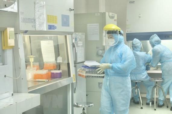 Nhân viên CDC Hà Nội làm xét nghiệm COVID-19. (Ảnh: Minh Quyết/TTXVN)
