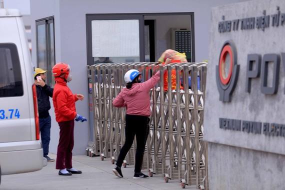 Người thân gửi đồ vào cho công nhân Công ty POYUN ở TP Chí Linh thời điểm mới bị phong tỏa - Ảnh: ANH CƯỜNG