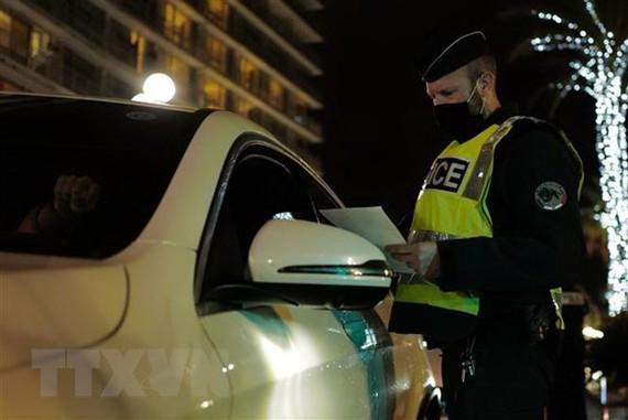 Cảnh sát kiểm tra giấy tờ của người lưu thông khi lệnh hạn chế được ban hành nhằm ngăn dịch COVID-19 lây lan tại Nice, Pháp. (Ảnh: AFP/TTXVN)