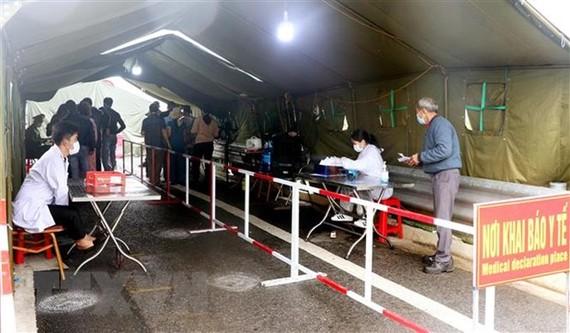 Chốt kiểm soát dịch COVID-19 tại chân cầu Bạch Đằng vẫn thực hiện khai báo đồng thời hai hình thức thủ công và điện tử. (Ảnh: Văn Đức/TTXVN)