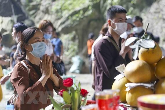 Du khách đến dâng lễ tại động Hương Tích tuân thủ việc đeo khẩu trang phòng dịch. (Ảnh: Tuấn Đức/TTXVN)
