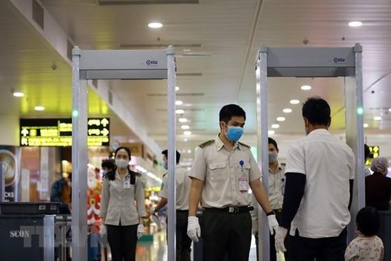Nhân viên an ninh hàng không kiểm soát hành khách tại khu vực soi chiếu. (Ảnh: Huy Hùng/TTXVN)