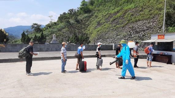 Cán bộ y tế phun thuốc khử khuẩn khu vực người dân làm thủ tục nhập cảnh ở cửa khẩu quốc tế Cầu Treo, Hà Tĩnh - Ảnh: DOÃN HÒA