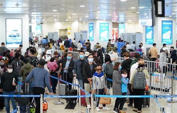 Hành khách tuân thủ việc đeo khẩu trang khi làm thủ tục chuyến bay tại Cảng hàng không quốc tế Nội Bài. (Ảnh: Phan Công/Vietnam+)